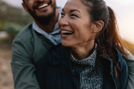 Photo for Smiling asian woman being embraced by her boyfriend from behind. Couple enjoying on vacation. - Royalty Free Image