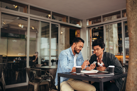 Photo for Two young men sitting together at coffee shop using mobile phone. Friends meeting at cafe and using smart phone. - Royalty Free Image