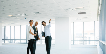 Photo pour Male real estate agent showing new office space to clients. Business people discussing and looking at new office with estate broker. - image libre de droit