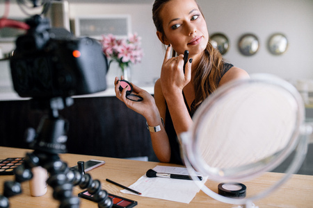 Foto de Fashion blogger recording video for her blog on cosmetics. Young woman applying makeup looking into a camera fixed on tripod. - Imagen libre de derechos