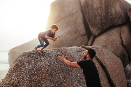 Foto de Outdoor shot of father and son having fun on summer holidays at the beach. happy little boy jumping into his father's arms from a rock. - Imagen libre de derechos