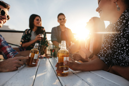 Photo pour Group of young people sitting around a table with drinks. Young men and women having rooftop party with focus on beer bottle. - image libre de droit