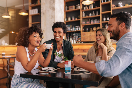 Foto de Young friends having a great time in restaurant. Multiracial group of young people sitting in a coffee shop and smiling. - Imagen libre de derechos