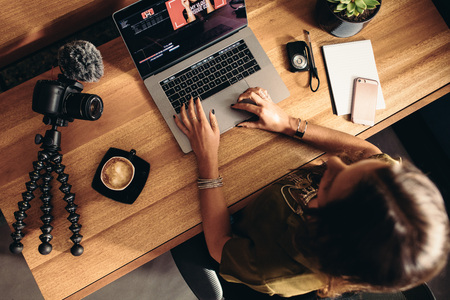 Photo for Top view of female vlogger editing video on laptop. Young woman working on computer with coffee and cameras on table. - Royalty Free Image