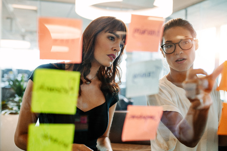 Foto de Asian businesswoman showing her coworker an idea posted on a sticky note wall. Creative professionals brainstorming on new business ideas. - Imagen libre de derechos