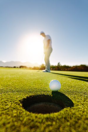 Photo pour Vertical shot of professional golfer putting golf ball in to the hole. Golf ball by the hole with player in background on a sunny day. - image libre de droit