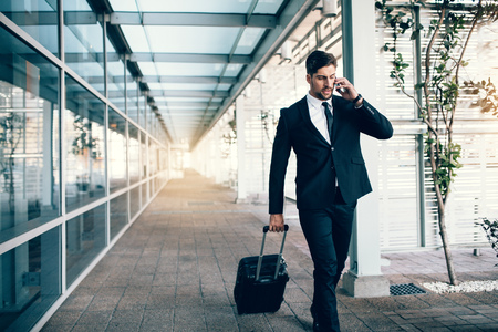 Photo pour Handsome young man on business trip walking with his luggage and talking on cellphone at airport. Travelling businessman making phone call. - image libre de droit