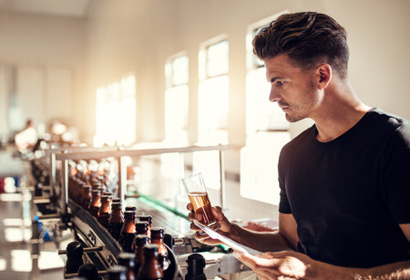 Photo pour Young man examining the quality of beer at brewery. Male inspector working at alcohol manufacturing factory checking the craft beer. - image libre de droit