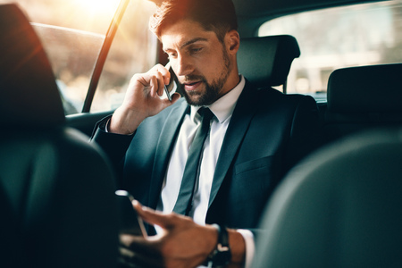 Foto de Young businessman talking on mobile phone and using tablet pc while sitting on back seat of a car. Caucasian male business executive travelling by a taxi and looking at digital tablet. - Imagen libre de derechos
