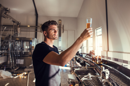 Photo for Young man examining the quality of craft beer at brewery. Male inspector working at alcohol manufacturing factory checking the beer. - Royalty Free Image