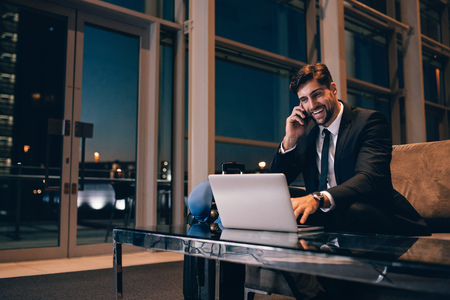 Photo pour Smiling businessman with laptop talking on cellphone at the airport waiting lounge. Handsome man at waiting room in airport terminal. - image libre de droit