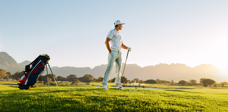 Photo for Full length of young man standing on golf course at sunset and looking away. Professional male golfer holding golf club on field. - Royalty Free Image