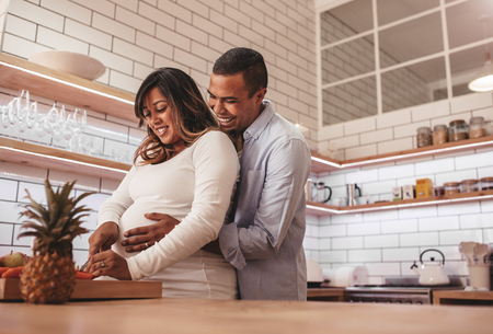 Photo pour Young couple cooking together in the kitchen while man embracing his pregnant wife. Happy young couple cooking food at home, chopping vegetable on kitchen counter. - image libre de droit