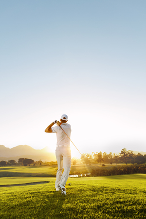 Photo pour Rear view of golfer hitting driver on a golf course in the sun. Full length shot of young man playing golf on a sunny day. - image libre de droit