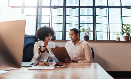 Foto de Shot of two young entrepreneurs sitting together at office  desk. Man showing something on clipboard to woman in office. - Imagen libre de derechos