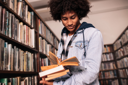 Photo for African male college student standing in library with lots of books. University student looking for study references. - Royalty Free Image