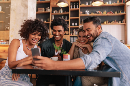 Foto de Group of young people sitting in a cafe and looking at the photos on smart phone. Young men and women sitting at cafe table and using cell phone. - Imagen libre de derechos