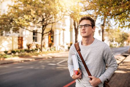 Photo pour Young caucasian male student with book outside on the road. Handsome young man going to college. - image libre de droit