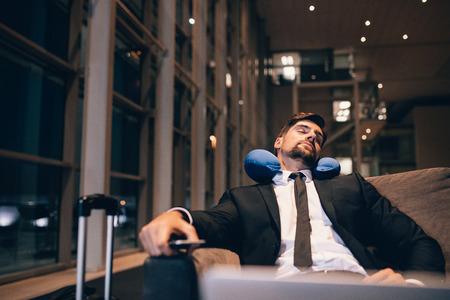 Foto de Traveler waiting at airport after flights delays and cancellations. Businessman asleep in airport lounge. - Imagen libre de derechos