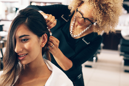 Foto de Closeup of a woman getting a stylish hairdo done at salon. Professional hair stylish pinning up the hair in stylish manner. - Imagen libre de derechos