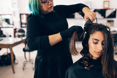 Photo pour Woman getting a hairdo at salon. Hair stylist turning straight hair into curly using a hair curling iron. - image libre de droit