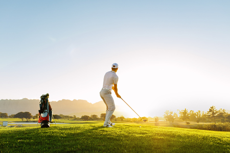 Foto de Full length of golf player playing golf on sunny day. Professional male golfer taking shot on golf course. - Imagen libre de derechos
