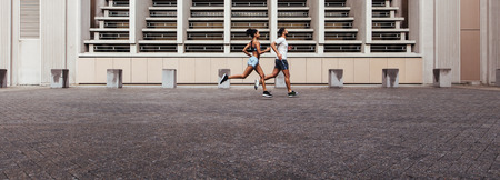 Photo pour Athletes running on street in the morning. Man and woman in jogging outfit running outdoors in the morning. - image libre de droit