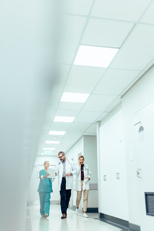 Photo pour Medical team discussing work while walking along the hospital corridor. Vertical image of medics briefing in hallway. - image libre de droit