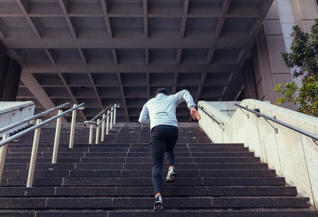 Photo pour Man running up the stairs of a building. Athlete climbing stairs as part of his physical training. - image libre de droit