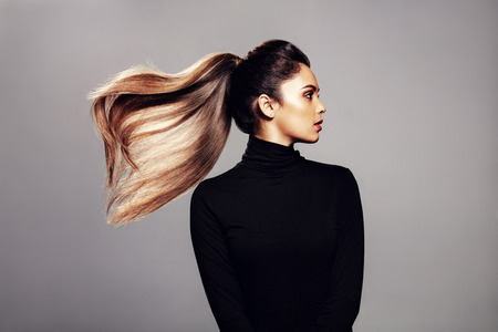 Foto de Studio shot of stylish young woman with flying hair against grey background. Female fashion model with long hair. - Imagen libre de derechos