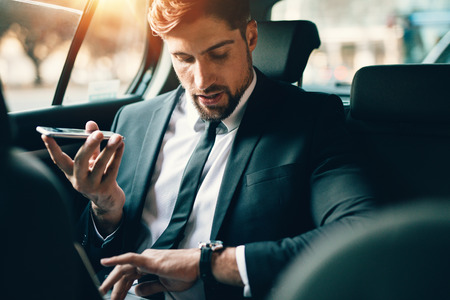Photo pour Handsome businessman talking on phone while sitting on the backseat of the car. Young man travelling by car using smart phone and checking time. - image libre de droit