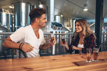 Foto de Couple at brewery toasting beers. Young man and woman tasting different varieties of craft beers. - Imagen libre de derechos
