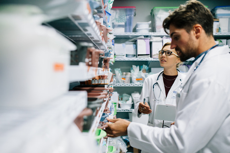 Foto de Two pharmacist working in drugstore. Male and female pharmacists checking medicines inventory at hospital pharmacy. - Imagen libre de derechos