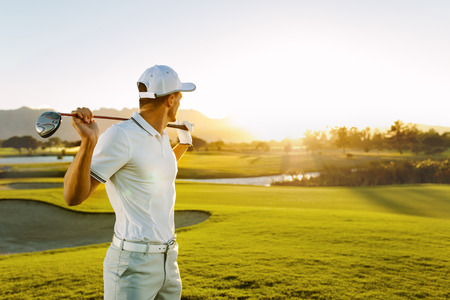 Foto de Shot of male golfer with golf club at course. Young man holding a golf club and looking away on a sunny day. - Imagen libre de derechos