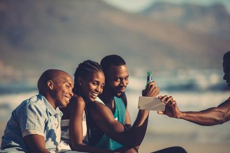 Foto de Group of happy friends having fun together and taking selfie using mobile phone. Self portrait at beach party. - Imagen libre de derechos