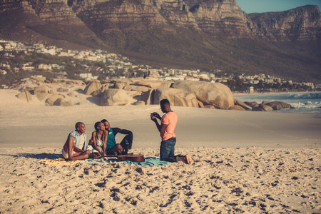 Foto de African young man photographing friends by phone outdoors at the beach. Handsome man taking picture of his friends from smartphone. - Imagen libre de derechos