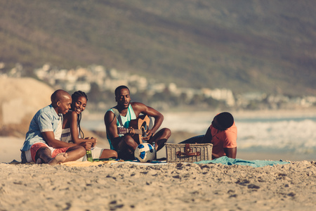 Photo pour Afro american young man with guitar singing a song for his friends. Group of friends on vacation relaxing at the beach. - image libre de droit