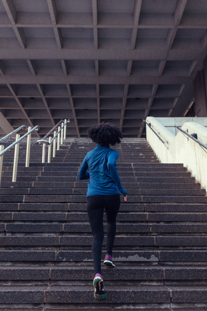 Photo pour Woman running up the stairs of a building. Woman athlete climbing stairs as part of her physical training. - image libre de droit