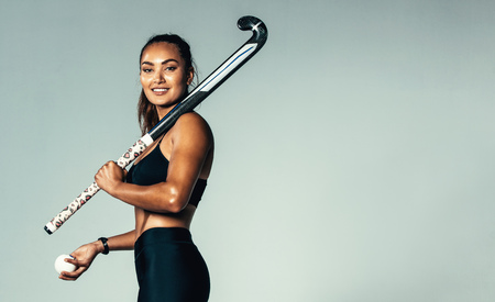Foto de Portrait of beautiful young woman holding hockey stick and ball against grey background. Hispanic female hockey player looking at camera. - Imagen libre de derechos