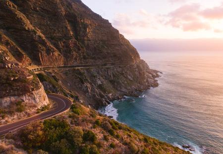 Foto de Beautiful road going along the mountain and oceans. Amazing sunset scene. - Imagen libre de derechos