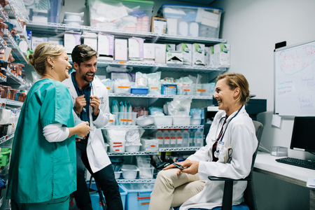 Foto de Hospital staff having casual discussion in the pharmacy. Three colleagues meeting in drugstore and laughing. - Imagen libre de derechos