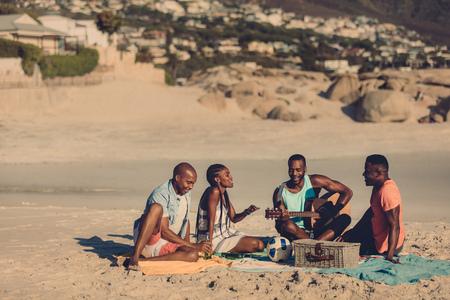 Foto de Group of friends with guitar sitting on beach. African people enjoying at the seaside picnic. - Imagen libre de derechos