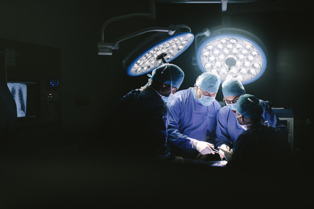 Photo for Medical team performing surgery. Group of surgeons in hospital operation theater. - Royalty Free Image