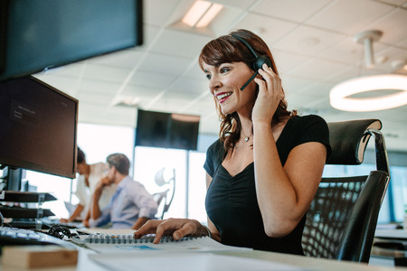 Photo pour Call center business woman talking on headset. Caucasian female in customer service position talking on the phone. - image libre de droit