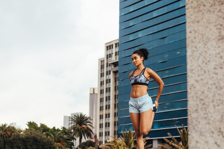 Photo pour Woman runner doing warm up exercises outdoors. Female athlete exercising outdoors with city buildings in the background. - image libre de droit