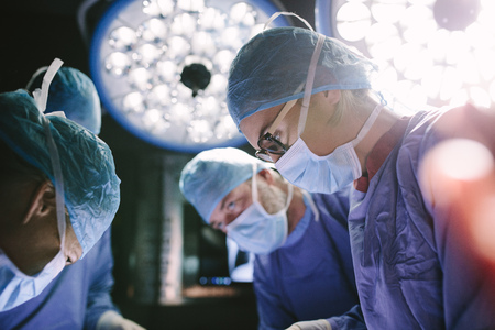 Photo for Concentrated female surgeon performing surgery with her team in hospital operating room. Medics during surgery in operation theater. - Royalty Free Image
