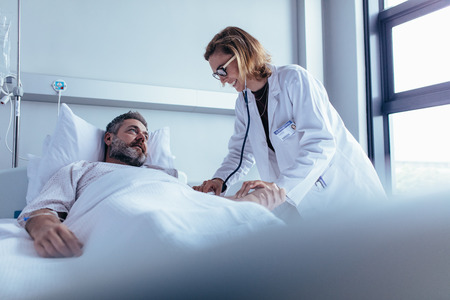 Photo for Hospitalized man lying in bed while doctor checking his pulse. Female physician examining male patient in hospital room. - Royalty Free Image