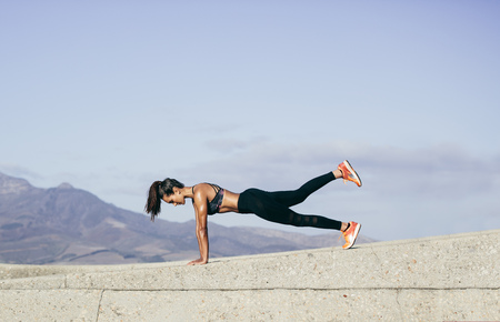 Photo pour Young muscular woman doing core exercise outdoors. Fit female doing press-ups during training session. Side view shot. - image libre de droit