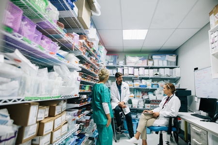 Photo pour Medical staff discussing in hospital pharmacy. Doctors and nurse talking in hospital pharmacy. - image libre de droit