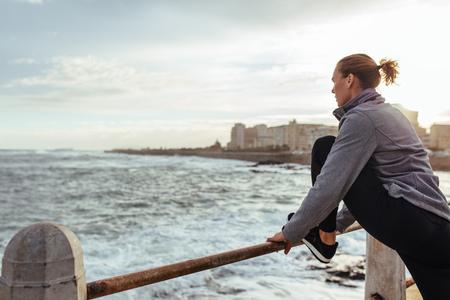 Foto de Healthy lifestyle. Woman in sportswear stretching her legs on railing at seaside promenade. - Imagen libre de derechos